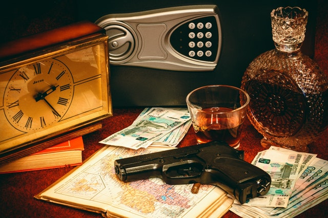 vault, gun, alcohol and money on a table